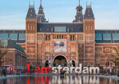 Rijksmuseum con el cartel I Amsterdam reflejadas en el agua