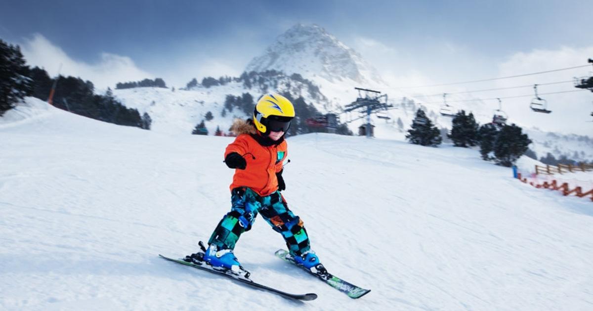Un pequeño esquiador de carreras en la nieve durante el puente de diciembre en España
